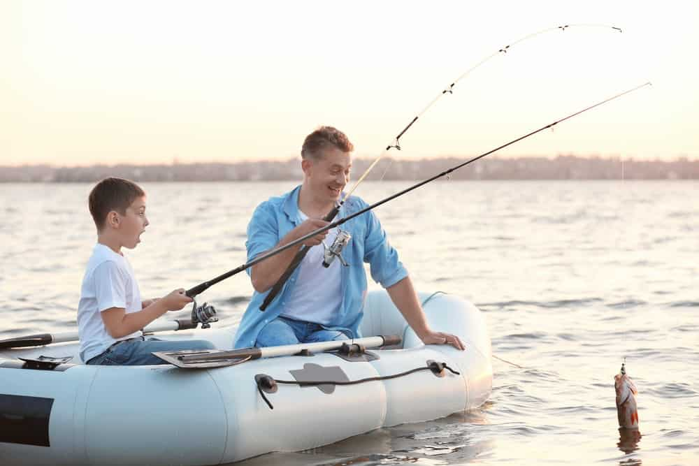 dad and son go fishing on inflatable boat