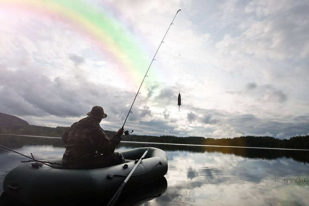 man fishing on a lake on The Sevylor Fish Hunter 360 inflatable boat