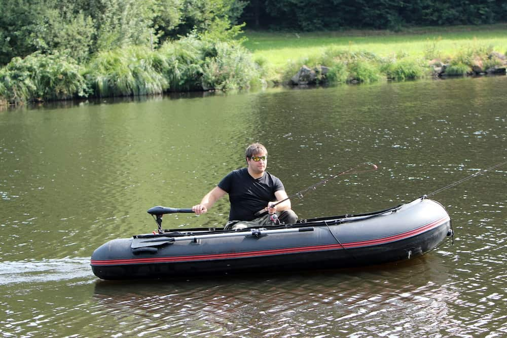 man fishing on an inflatable boat with a trolling motor