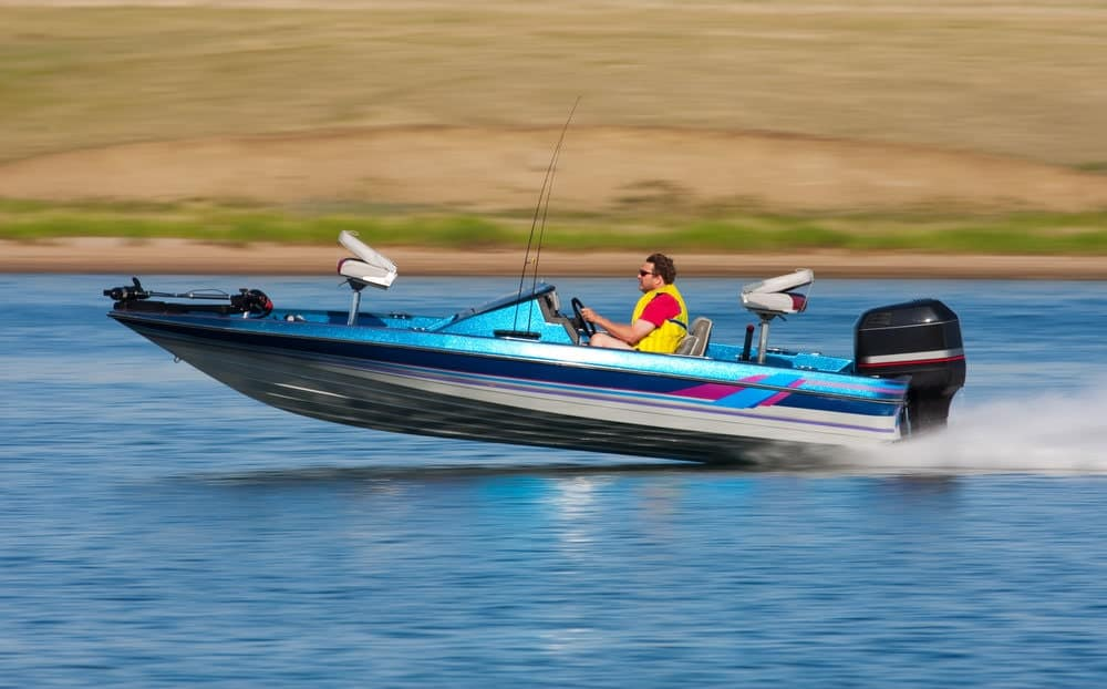 man riding boat with outboard motor at high speed