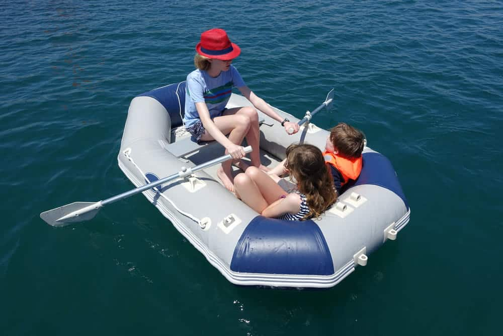 Three children having fun in an inflatable boat