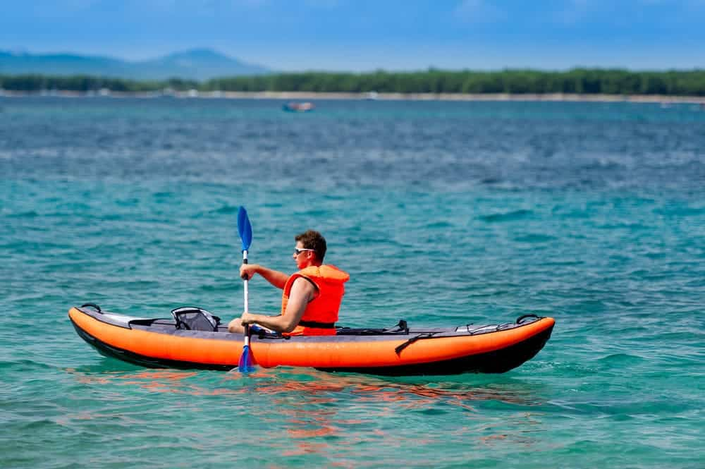 a man using inflatable kayak on the sea