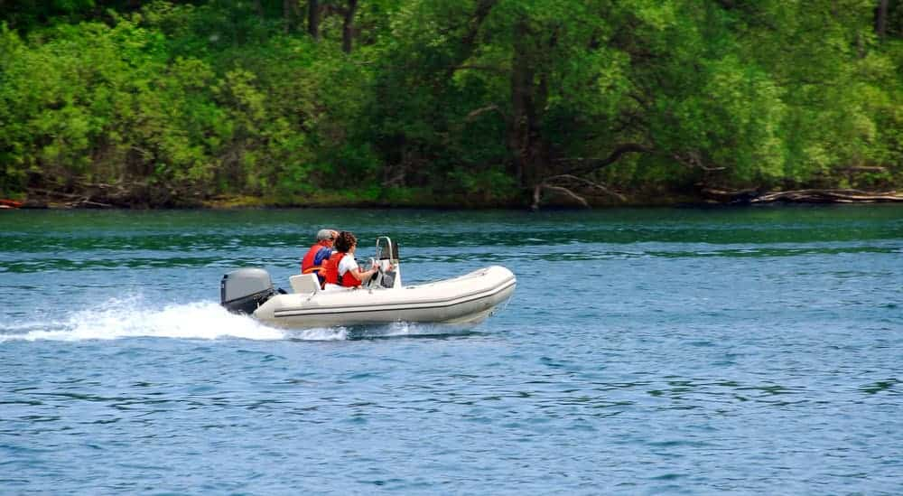 couple driving hard bottom inflatable boat on a river