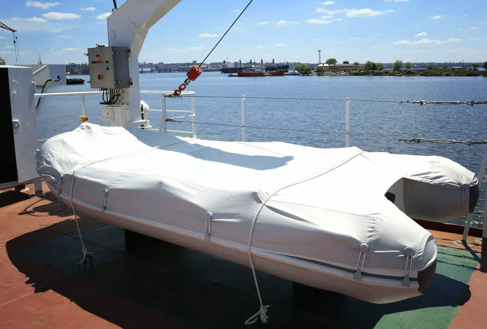 inflatable boat using gray boat cover on ship deck