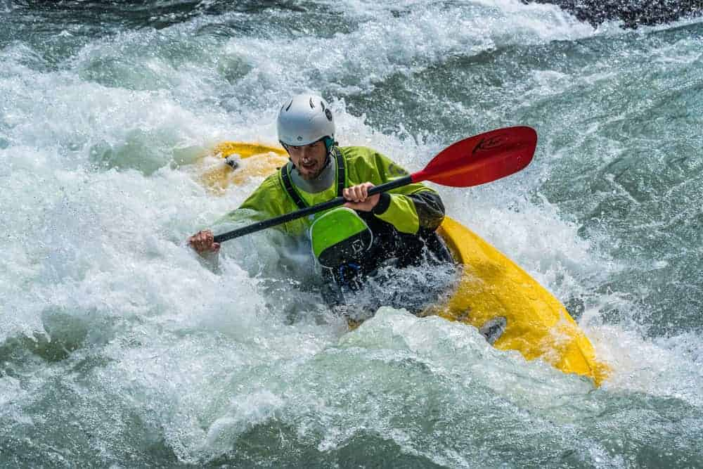 man in inflatable boat kayaking on white water