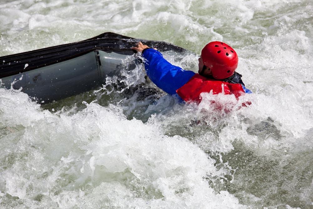 man sinking in white water while kayaking