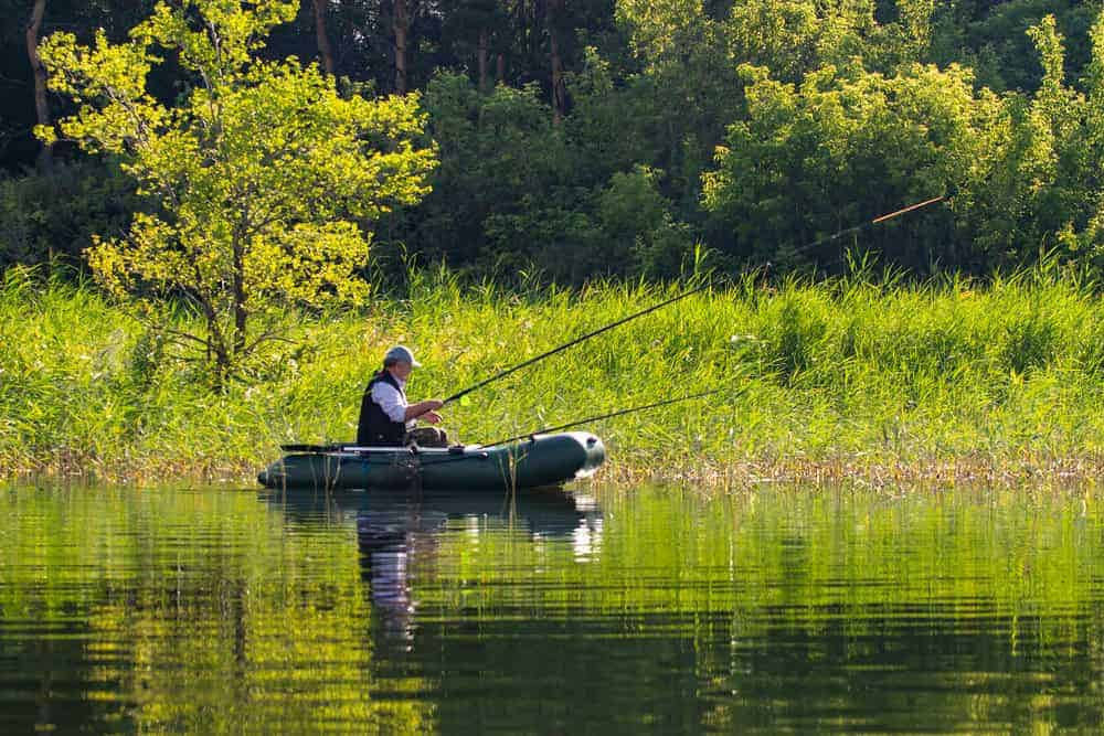 senior man fishing on an inflatable boat with trolling motor