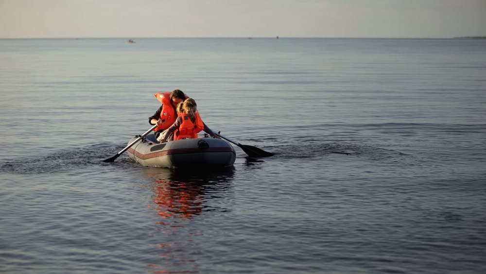 woman and girl in life jackets rowing inflatable boat on a sea