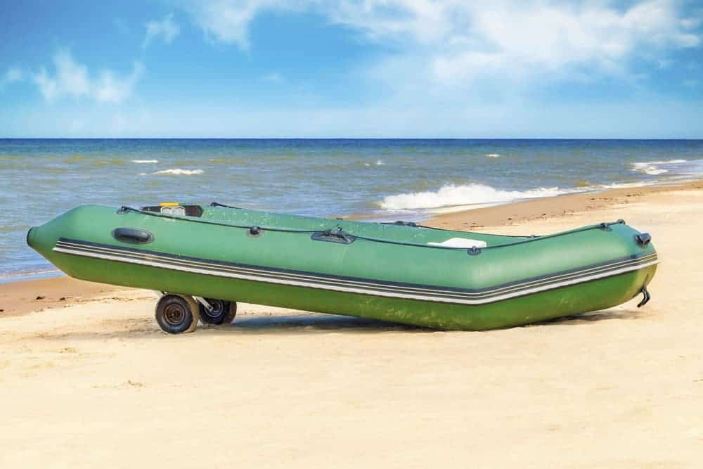 an inflatable boat with transom wheels on the shore