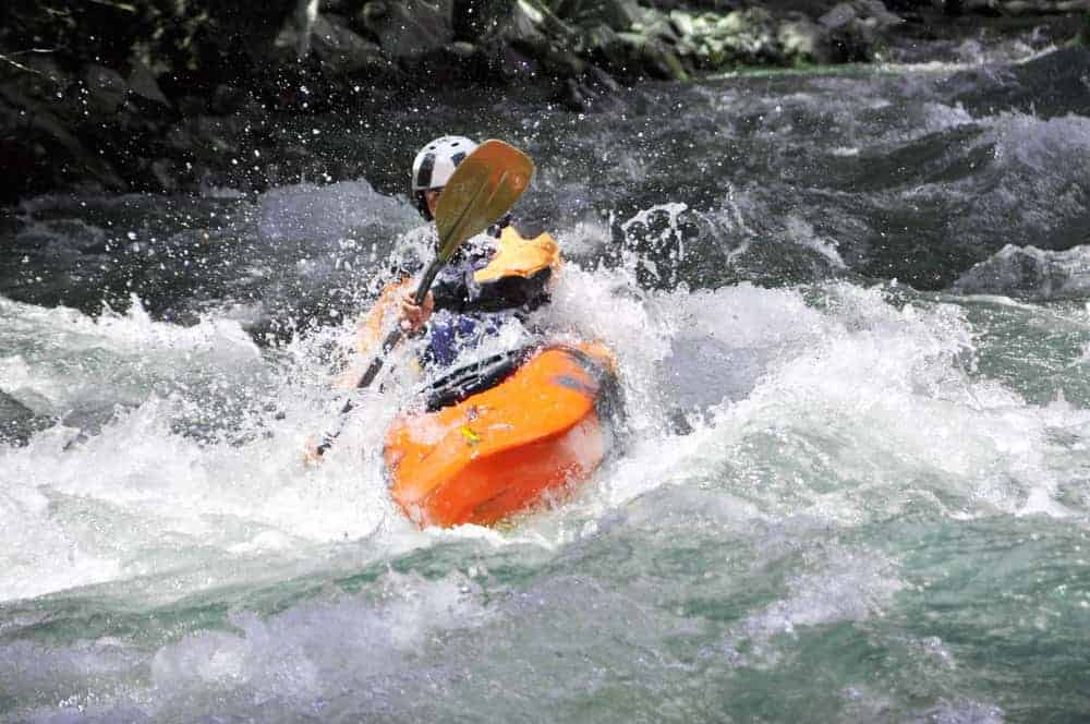 man kayaking with a short paddle in whitewater