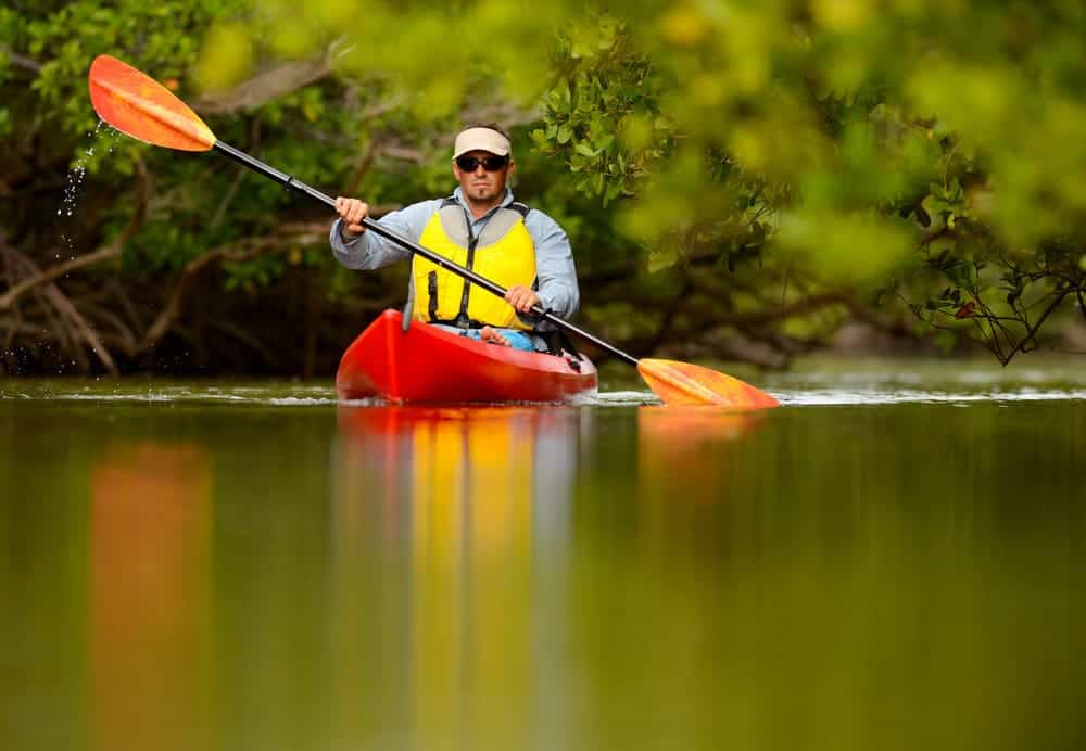 man rowing on a river with a long paddle