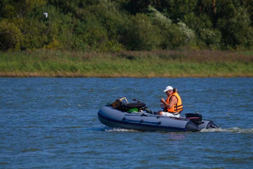 senior man on inflatable boat equipped with trolling motor and battery
