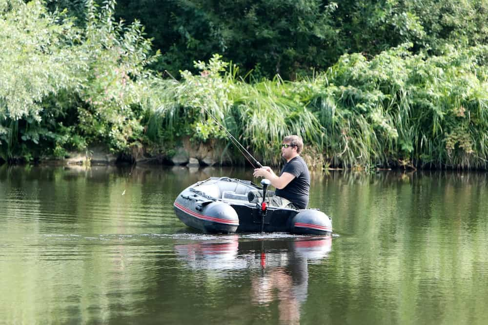 young man fishing with remote control trolling motor