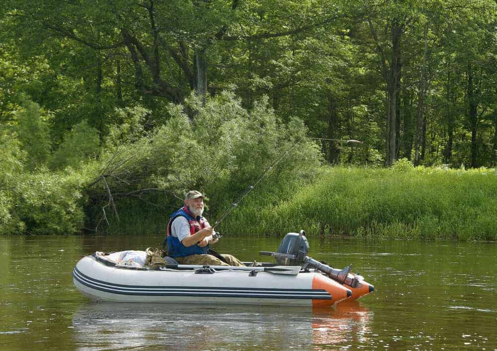 seninor man going fishing on inflatable boat with outboard motor