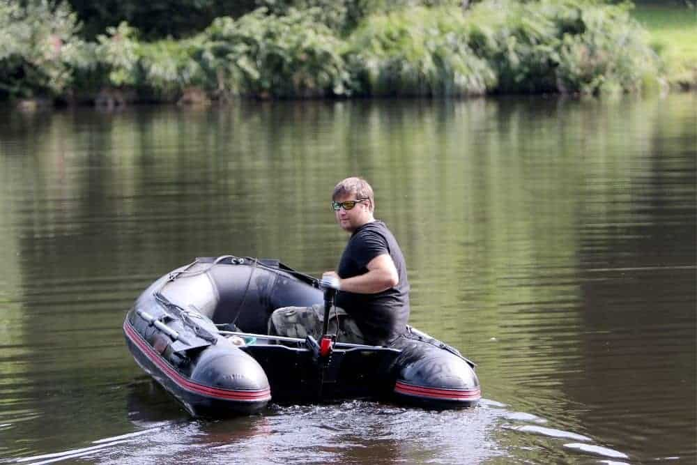 a young man going fishing on an inflatable boat with trolling motor