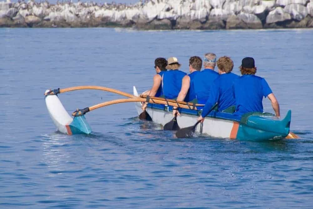 a group of people trolling on a kayak with an outrigger