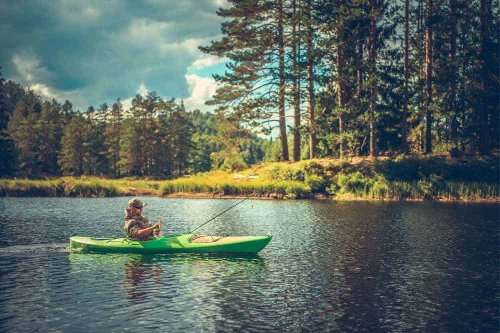man on a green kayak with trolling motor fishing on a river