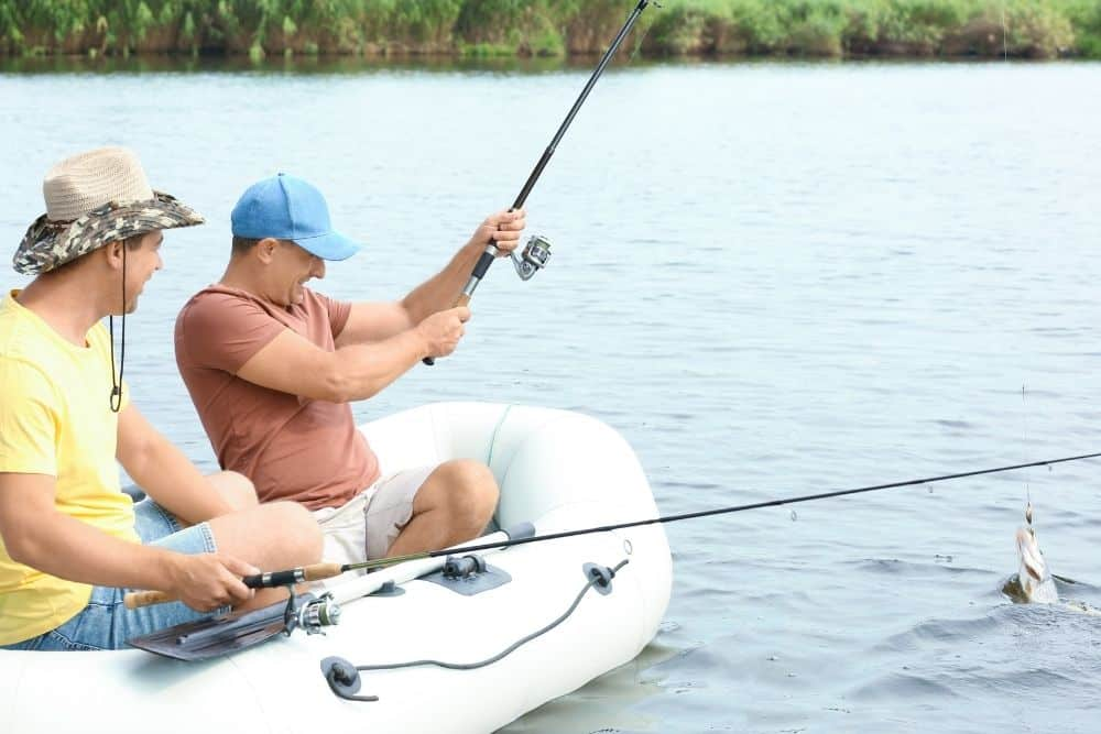 2 young men fish in an inflatable boat