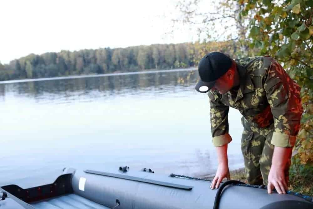 man checking leaks in an inflatable boat