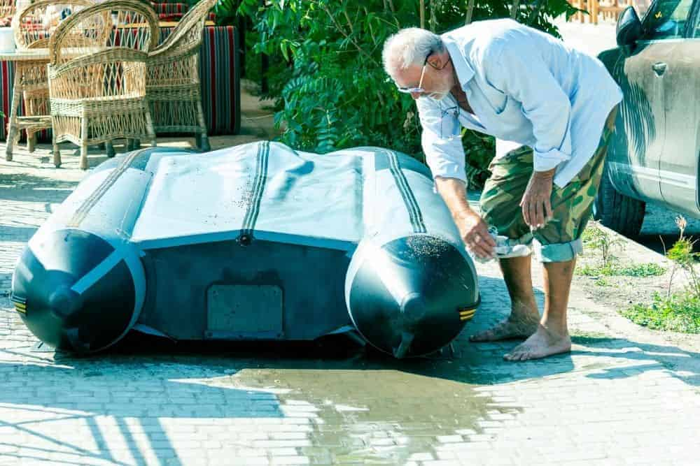 old man repairs the broken transom on an inflatable boat