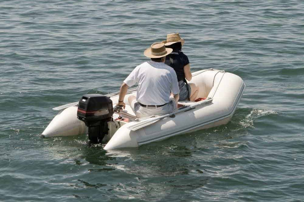 a couple in an inflatable boat using outboard motor