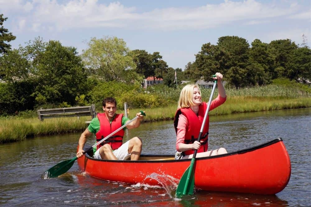 a couple paddling on a red canoe