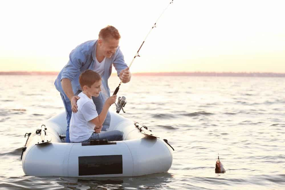dad and son are fishing on a lake with a white inflatable boat