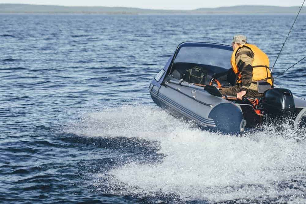 man driving fast in inflatable boat on the ocean