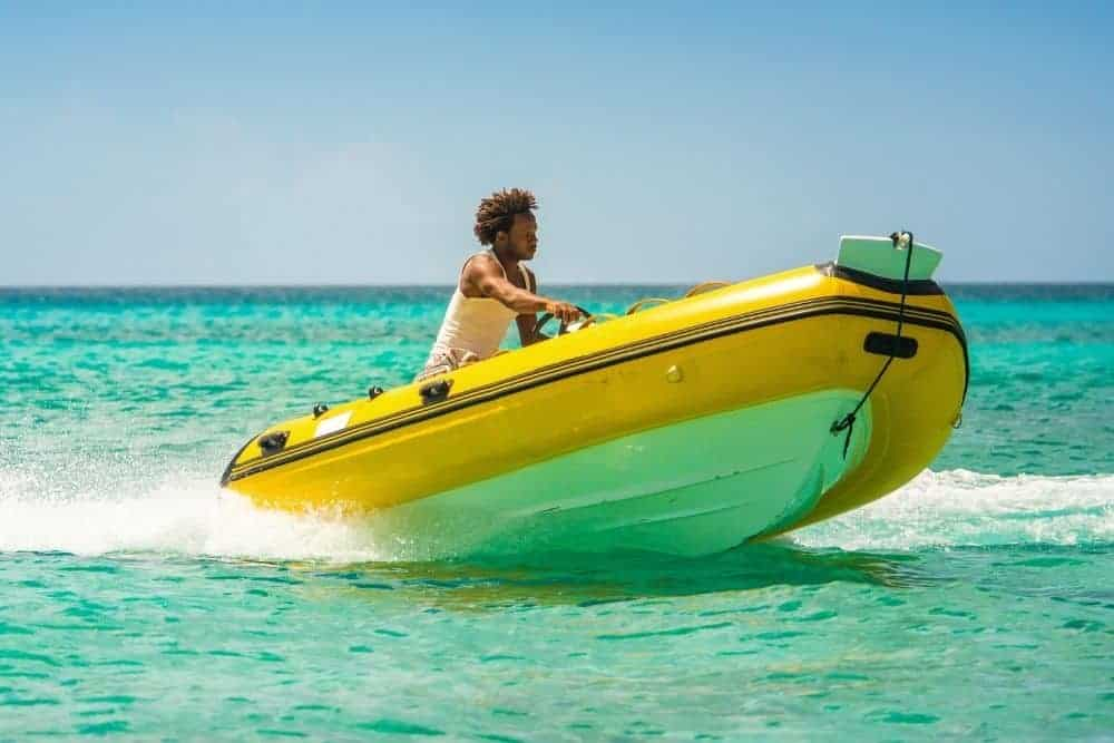 a black man driving a yellow RIB with heavy hull on ocean