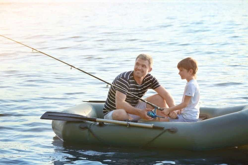 father and son going fishing on a green inflatable boat