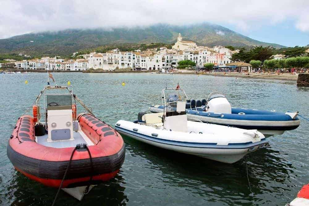 red, white, blue rigid inflatable boats at the dock
